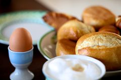 Boiled egg with bread rolls. Breakfast of boiled egg with fresh bread roll and cup of frothy, milky coffee Stock Photo