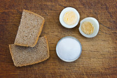 A boiled egg, bread and salt. On a wooden table Stock Photos