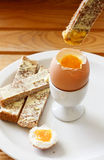 Boiled egg and buttered toast. A buttered toast soldiers being dipped into a soft boiled egg in an egg cup Royalty Free Stock Photos