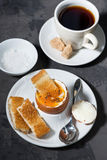 Boiled egg, cup of coffee and crispy bread, top view Royalty Free Stock Photo