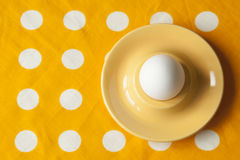 A boiled egg in an egg cup on yellow rumpled dotted cloth. Minim Stock Images