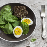 Boiled egg and fresh spinach on a brown plate Stock Photo