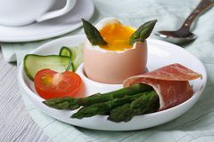 Boiled egg with green asparagus, ham and vegetables closeup Stock Image
