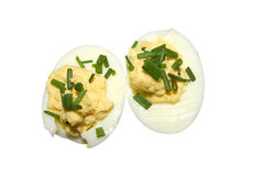 Boiled egg halves with garnish isolated. Salad accompaniment of boiled egg halves with spring onion garnish isolated on a white background Royalty Free Stock Photography