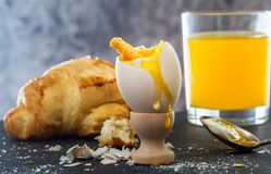 Boiled egg with liquid yolk, croissant, a glass of fresh juice. Simple breakfast royalty free stock image