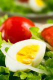 Boiled egg on a plate with lettuce, onions and cherry tomatoes Royalty Free Stock Photography