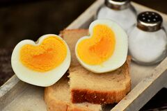 Boiled Egg on Top on Bread Beside Salt Shaker Stock Images