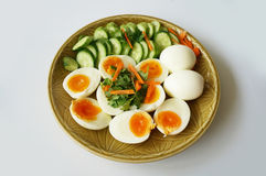 Boiled egg with vegetables. A photo of Hard - boiled eggs with cucumber, carrot and coriander on plate isolated on white background, close up Royalty Free Stock Photo