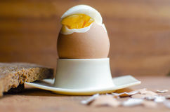 Boiled Egg In White Cup. Boiled egg on color wooden background Stock Image