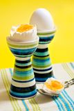 Boiled eggs. In tall striped egg-cup stock photo