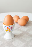Boiled eggs. Single boiled egg in a holder and a group of three eggs in the background Stock Photos