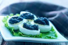 Boiled eggs with caviar Stock Images