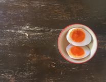 Boiled eggs are divided into two pieces in a cup on a wooden table. royalty free stock photography