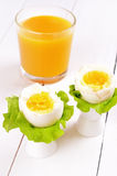 Boiled eggs in egg cups and orange juice Royalty Free Stock Images