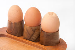 Boiled eggs in egg holder with cracked egg Stock Photography