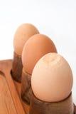 Boiled eggs in egg holder with cracked egg Stock Images