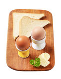 Boiled eggs in eggcups and white bread. Boiled eggs in eggcups and slices of white bread Royalty Free Stock Photography