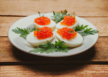 Boiled eggs half with red salmon caviar Stock Images