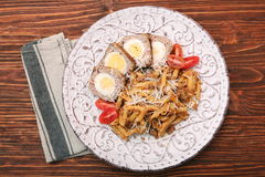Boiled eggs in a layer of sausage meat wrapped with pasta Stock Images