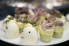 Boiled eggs and octopus snacks in glasses on a blurred background. royalty free stock photos