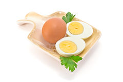 Boiled eggs. One egg, two halves of boiled eggs and parsley on the plate Stock Photo
