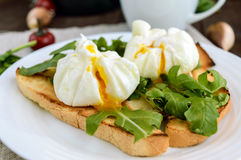 Boiled eggs in a pouch (poached) on crispy toast and green arugula leaves. Dietary breakfast. Stock Images