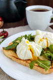 Boiled eggs in a pouch (poached) on toast and crisp green leaves of arugula and a cup of tea. Royalty Free Stock Photo