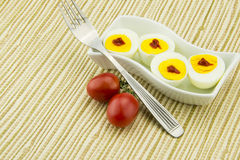 Boiled eggs, red cherry tomatoes Royalty Free Stock Image