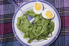 Boiled eggs with spinach pasta Royalty Free Stock Photos
