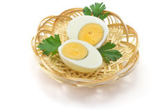 Boiled eggs. Two halves of boiled eggs and parsley leaves in a straw plate Stock Image