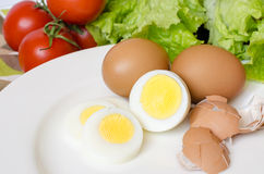 Boiled eggs with vegetables. Boiled eggs on a white plate surrounded by vegetables Royalty Free Stock Photos