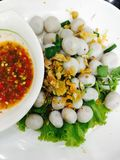 Boiled fish ball with vegetables, fried garlic and spicy sauce. Food snack Royalty Free Stock Photo