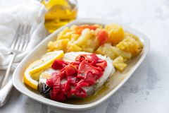 Boiled fish with red pepper, vegetables and olive oil on white dish royalty free stock image