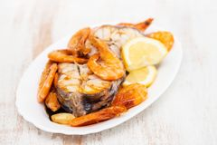 Boiled fish with shrimps and lemon on white dish Royalty Free Stock Photo