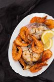 Boiled fish with shrimps and salad on white dish Royalty Free Stock Photo