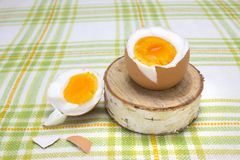 Boiled fresh egg for the breakfast on the wooden birch stand for eggs. Broken beige hen egg and pieces of shells, bright orange yo. Lk Stock Photos