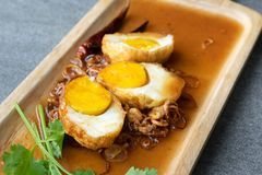Boiled and Fried eggs in sweet and sour sauce with coriander in the wooden dish on table.  royalty free stock image