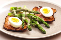 Boiled green asparagus with bacon, egg and mustard dip. Inside, indoors, interiors, gastronomy, cuisine, food, meal, nutrition, nourishment, plate, vegetable stock photos