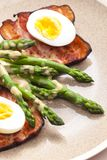 Boiled green asparagus with bacon, egg and mustard dip. Inside, indoors, interiors, gastronomy, cuisine, food, meal, nutrition, nourishment, plate, vegetable stock photo