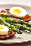 Boiled green asparagus with bacon Stock Image