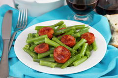 Boiled green beans with fried sausages Stock Photos