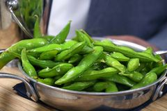 Boiled green soybeans in the pod ready for eating. Boiled green soybeans in the pod serving in metal plate, ready for eating royalty free stock image