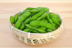 Boiled green soybeans in a small bamboo basket. Boiled green vegetable soybeans (edamame) in a small bamboo basket. Often found in Japanese restaurants and some Stock Image