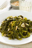 Boiled greens with nuts and garlic on white plate Royalty Free Stock Images