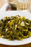 Boiled greens with nuts and garlic on white plate Royalty Free Stock Image