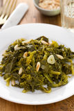 Boiled greens with nuts and garlic on white plate Royalty Free Stock Photography