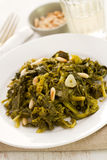 Boiled greens with nuts and garlic on white plate Royalty Free Stock Photo