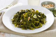 Boiled greens with nuts and garlic on white plate Stock Photography
