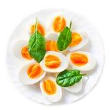 Boiled ha diviso in due le uova sul piatto decorato con il isolat delle foglie degli spinaci Immagini Stock Libere da Diritti