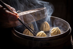 Boiled and hot chinese dumplings in wooden steamer. On wooden table Stock Images